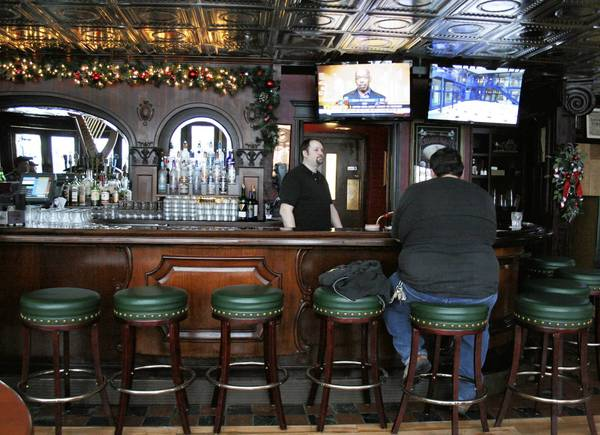 Bartender Andy Sibben tends to a customer at McGovern's Public House in January. The pub closed in the beginning of July because of the lack of business, which was hindered by nearby road closures.