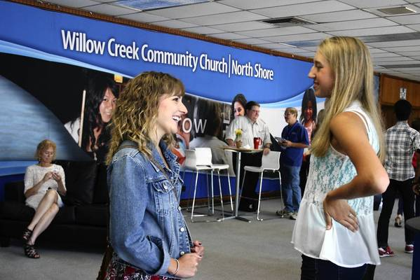 Deerfield resident Nikkie Haines, 20, left, talks to her friend Anna Schmeissing, 17, after a Sunday service at Willow Creek Community Church in Northfield on Aug. 18.