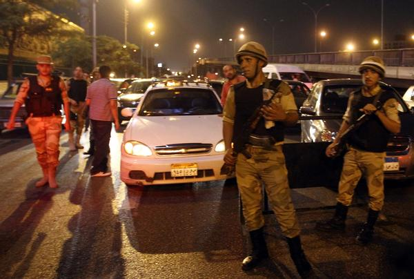 Egyptian troops search vehicles at a checkpoint during a curfew in Cairo imposed by the country's military-backed leaders.
