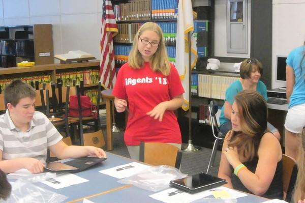 Lake Zurich Community Unit School District 95 iAgent Megan Kalafut (center), 15, helps Isaac Dina (left), 14, and Hannah Craig (right), 15, set up their iPads earlier this month.