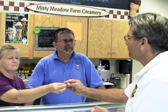 Betsy Herbst, left, hands a sample of ice cream from Misty Meadow Farm Creamery to Maryland Agriculture Secretary Buddy Hance, right, as David Herbst looks on. The Herbsts own the creamery, which is one of eight dairy farms across the state that produce ice cream and sell it directly to customers.