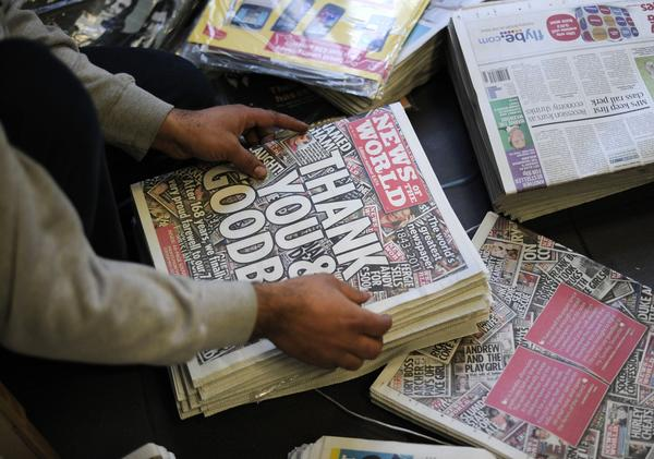A man prepares copies of the last edition of the British tabloid News of the World for sale at a shop in south London on July 10, 2011. Revelations of phone hacking by journalists at the paper triggered an investigation into media misconduct.