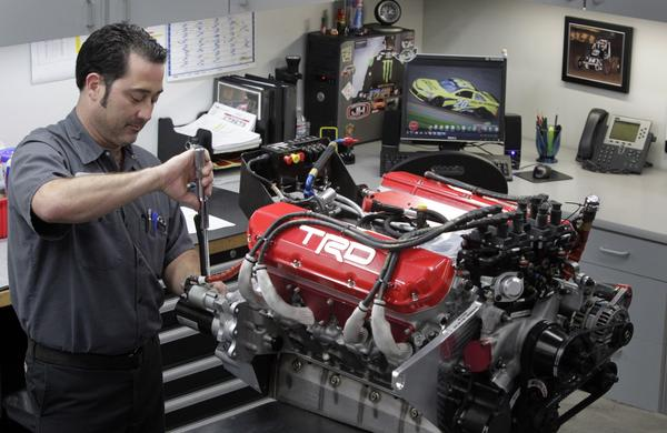 Toyota Racing Development technician J.J. Ercse tightens a bolt with a torque wrench while doing final preparation work on an engine that will be used in a NASCAR race.