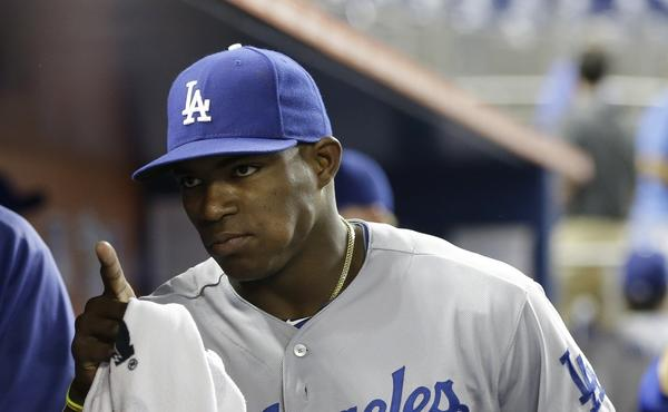 Dodgers outfielder Yasiel Puig gestures in the dugout before Tuesday's game against the Miami Marlins. Puig, who didn't start the game, was fined by the team for arriving late to the ballpark.