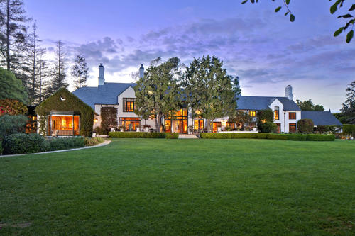 The estate is set back beyond a flat expanse of lawn.