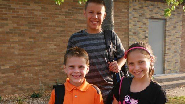 Nathan Woessner, 6, in orange, stands with his siblings on the first day of school.