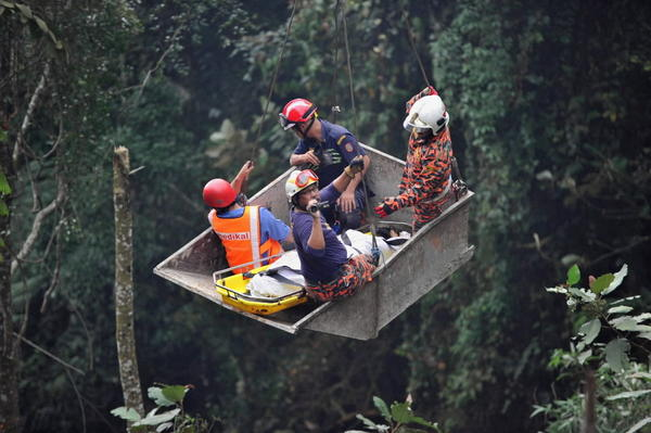 Malaysian emergency services personnel rescue a passenger (C) after a bus carrying tourists and local residents fell into a ravine near the Genting Highlands, about an hour's drive from Kuala Lumpur.