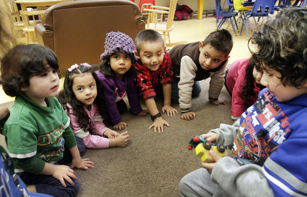 "Pre-Schoolers in ""toy sharing"" learning exercise at Pacific Asian Consortium in Employment Early Childhood Education program in Los Angeles."