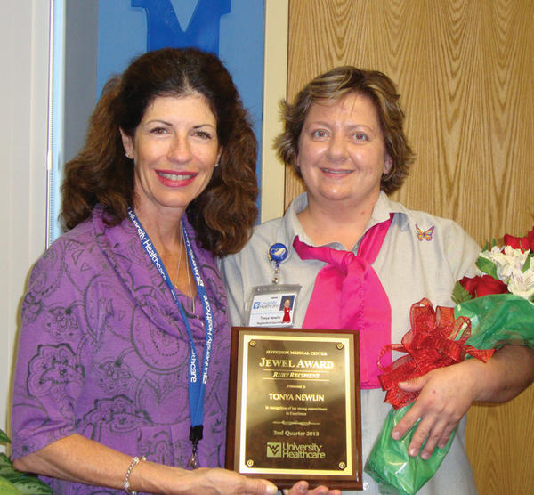 Christina DeRosa, chief administrative officer at Jefferson Medical Center, presents the Ruby Award to Tonya Newlin, registration specialist at the medical center.