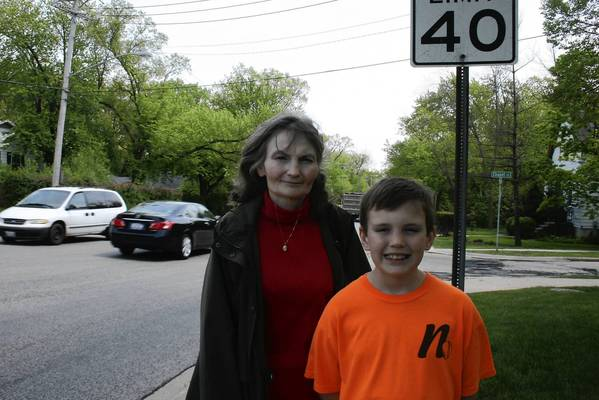 Northbook resident Sheila Czajka, left, and her son Richie stand near a speed limit sign at the intersection of Shermer and Waukegan roads on May 20. Czajka and other neighbors in the area are now urging the speed limit on Shermer Road to be decreased from 30 mph to 25 mph.