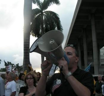 Activist Michael Rajner exhorting people with two bullhorns at March 2011 protest rally.