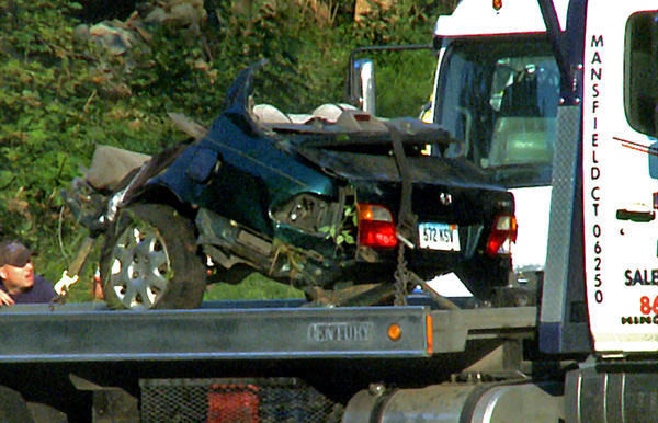 The rear half of the car involved in Wednesday's accident is placed on a flat bed truck.