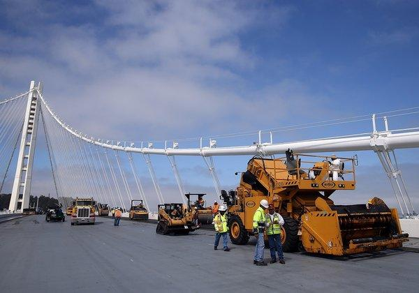 Workers pave the deck of the eastern span of the newly constructed San Francisco-Oakland Bay Bridge.