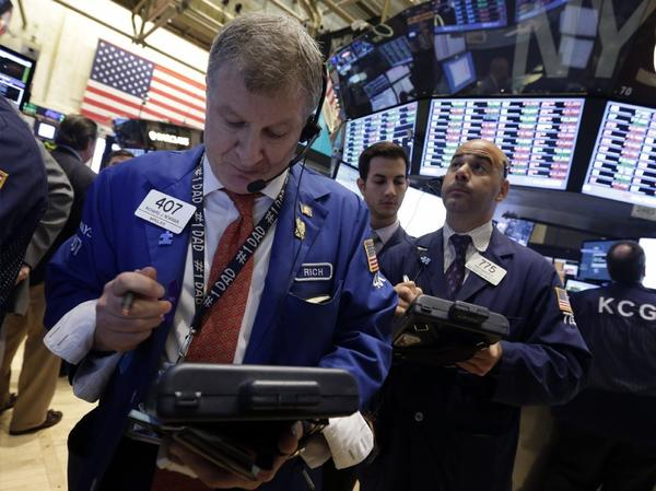 Mounting expectations that the Fed will start to reduce its monetary stimulus next month has weighed on markets. Above, traders work on the floor of the New York Stock Exchange.