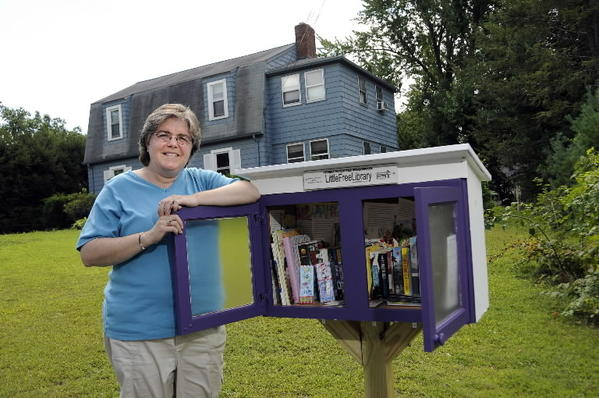 Mary Fournier stands next to the Little Free Library that she erected in the front yard of her Enfield home.