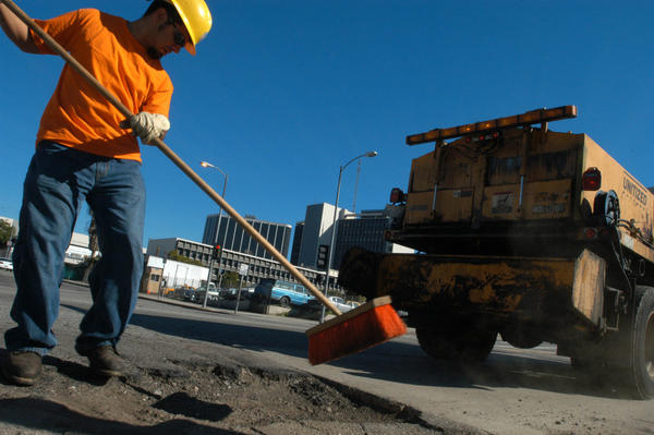Ozzie Haro prepares a pot hole to be filled in 2005. Since 2005, the city has paid for normal upkeep and maintenance on streets of good quality, but has left a backlog of severely damaged roads largely untouched.