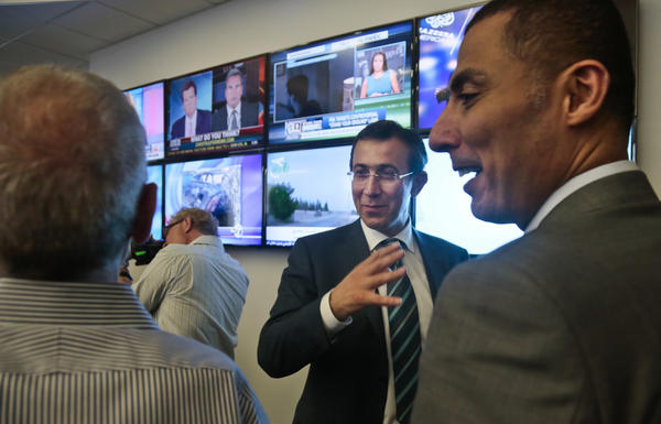 Ehab Shihabi, second from right, interim CEO for Al Jazeera America, gestures as he chats with newsroom staff after the network's first broadcast.