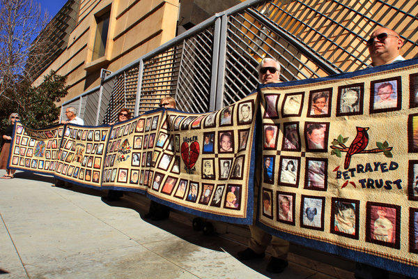 Quilts depicting victims of sexual abuse by priests are held up by victims and their supporters at the Cathedral of Our Lady of the Angels in Los Angeles.