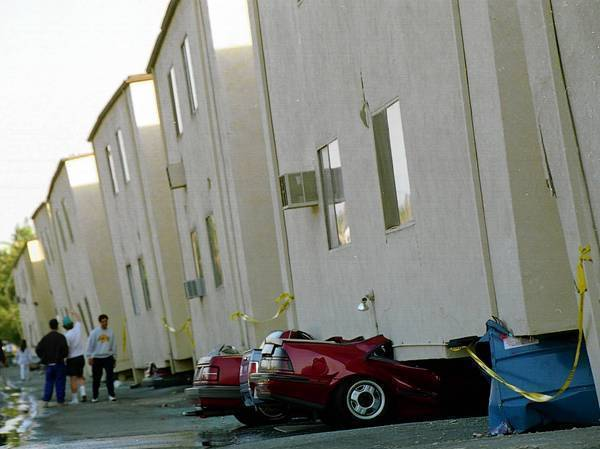 Cars are crushed underneath tilted apartment buildings after the 1994 Northridge earthquake.
