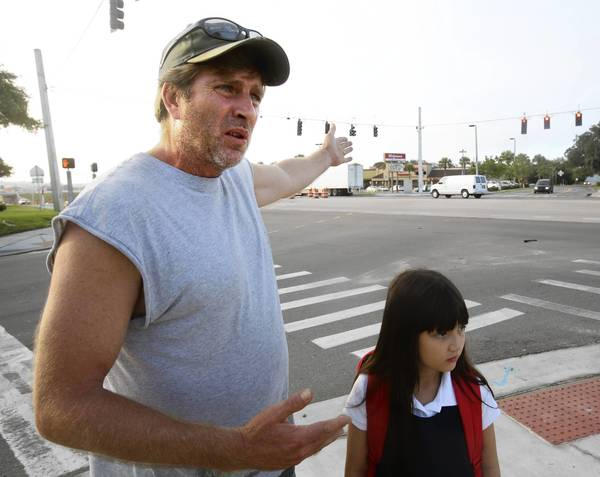 Mike Hayden walks his daughter Destin, 7, across SR 50 on their way to Clermont Elementary.