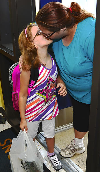 Mom Anita Clutter gives a goodbye smooch to her daughter, Brianna Lauziere, Wednesday at Potomac Heights Elementary School. Brianna entered third grade Wednesday.