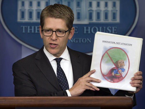 "White House press secretary Jay Carney holds up a folder with an image of a troll and the words ""innovation, not litigation."" The Obama administration seeks to limit frivolous patent lawsuits."