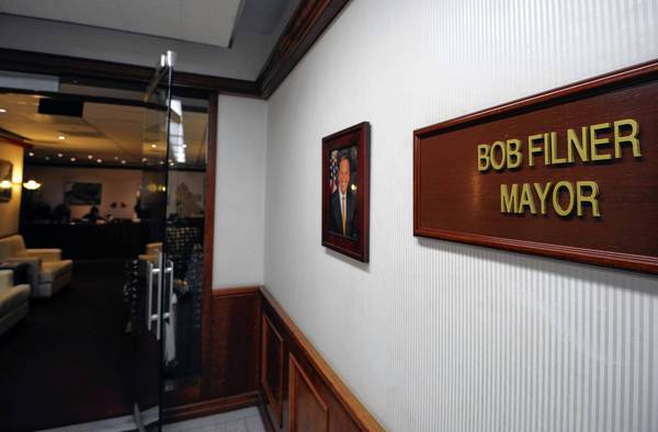 A sign and a portrait hang on the wall outside the office of San Diego Mayor Bob Filner, who has rejected widespread demands for his resignation.