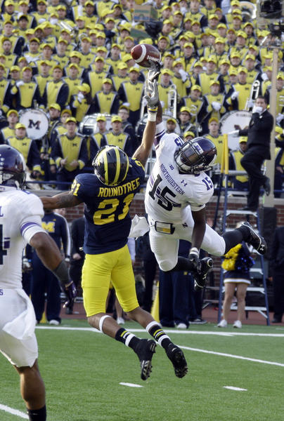 Northwestern's Daniel Jones leaps for a pass that Michigan's Roy Roundtree caught off the deflection.