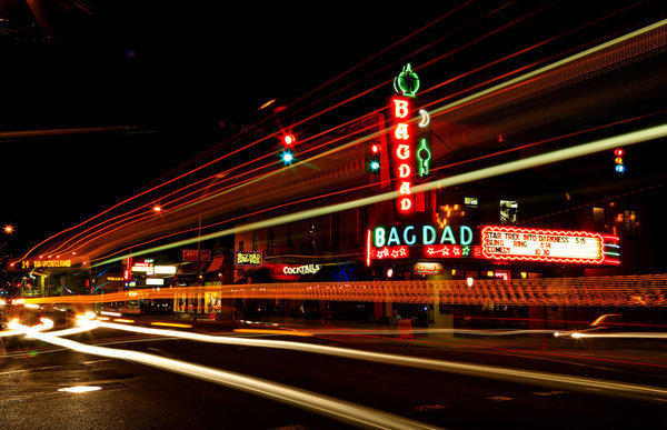 Lights from cars and buses streaking past the Bagdad add to the allure of the neon-bedazzled theater in Portland, Ore.