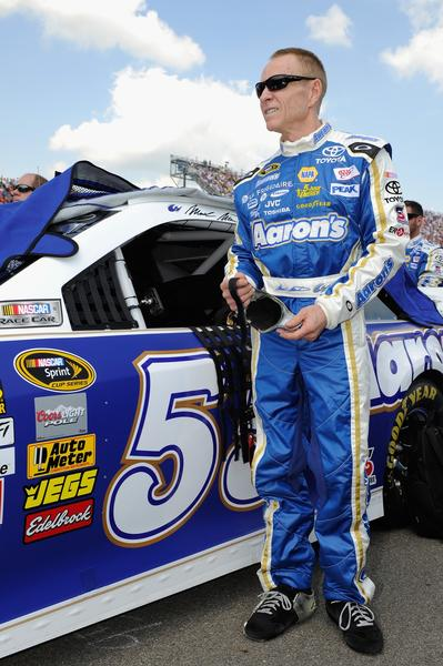 Mark Martin, driver of the #55 Aaron's Dream Machine Toyota, stands on the grid during prerace ceremonies for the NASCAR Sprint Cup Series 44th Annual Pure Michigan 400 at Michigan International Speedway.