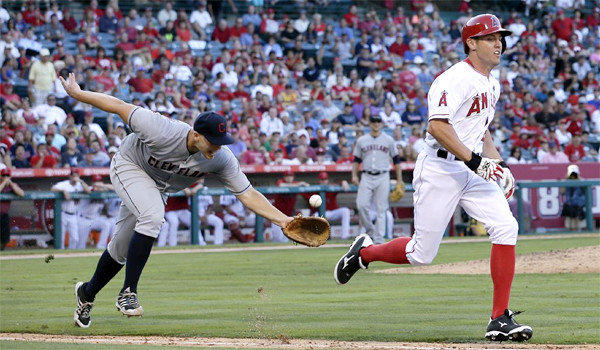 Cleveland pitcher Justin Masterson, left, tosses the ball to first baseman Nick Swisher for the out on Angels center fielder Peter Bourjos, right, during the seventh inning of the Indians' victory, 3-1.