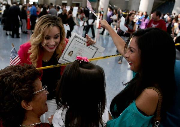 Lizbeth Lopez, a native of Mexico, is congratulated by mother Grace Lopez, daughter Damaris Lopez and sister Susie Lopez after getting her American citizenship at a naturalization ceremony in the Los Angeles Convention Center.