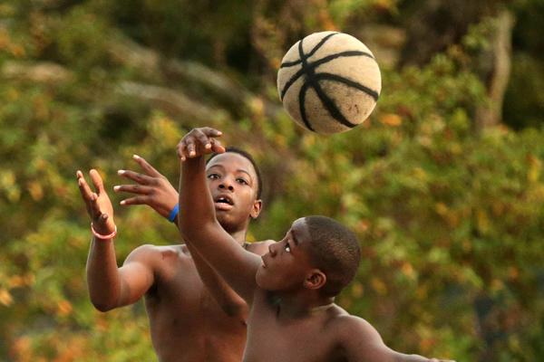 Lamarc Johnson, 14, left, and Daviontay Stokley, 12, reach for a loose ball while playing an early morning game of basketball with friends on Thursday at at Ogden Park in Chicago.