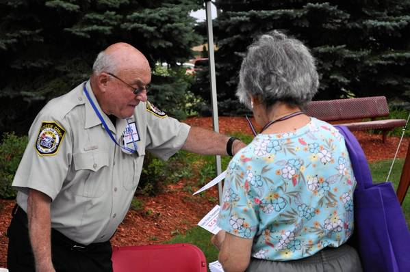 Len Cohen, a volunteer with Niles Police Service Members, answers crime prevention questions at the city's Aug. 6 National Night Out.