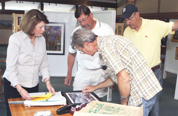 Suzanne LaBeau of Petoskey (from left) Mark Haveman of Atwood and Joe Abdella of Boyne City look as Maurice Seaman of Charlevoix explains the photo he is checking in for the photography exhibition at Charlevoix Circle of Arts. The theme My Michigan rallied photos from across the area for the contest organized by the Charlevoix Photography Club and sponsored by the Charlevoix Circle of Arts.