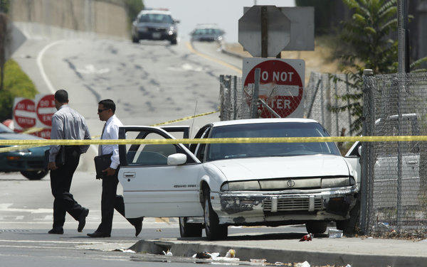 LAPD officers investigate the end of a car-to-car shooting the occurred on the northbound 110 Freeway in South Los Angeles between Manchester and Florence avenues.