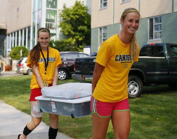 Sabrina Fitzgerald, left, and Katelyn Felegy help carry belongings into Frisch Residence Hall as freshmen students move into the dormitories at Canisius College in Buffalo, N.Y.