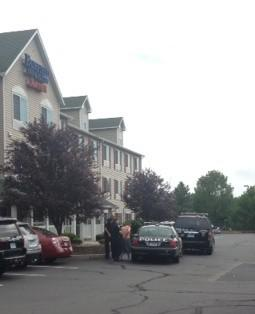 Police had gotten this unidentified man into some shorts before loading him into a cruiser outside the Fairfield Inn.