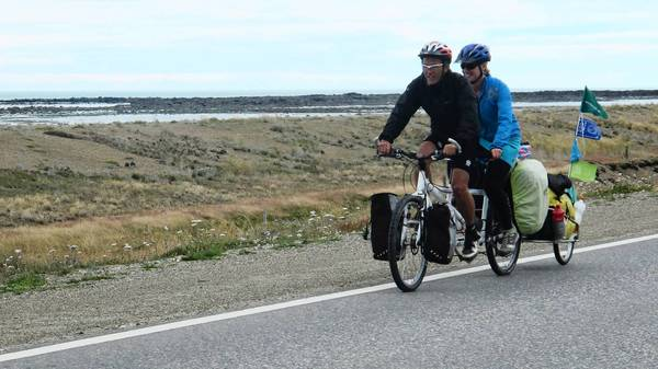 Tauru Chaw (front) and Christi Bruchok ride their tandem bike along the Atlantic coast in Tierra del Fuego in South America early in their 16,000-mile journey.