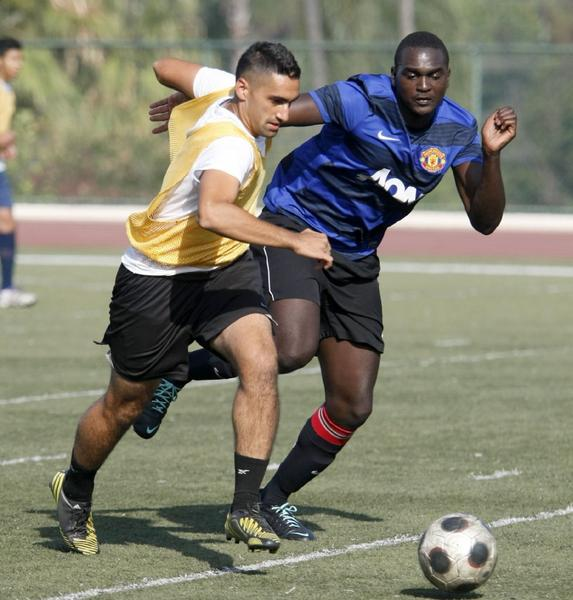 Glendale Community College soccer player Raimond Baghoomian, left, chases after the ball with teammate Fafana Indussa, right, during practice at the school's field on Tuesday. The Vaqueros are hoping for a bounce-back 2013 campaign. (Raul Roa/Staff Photographer)