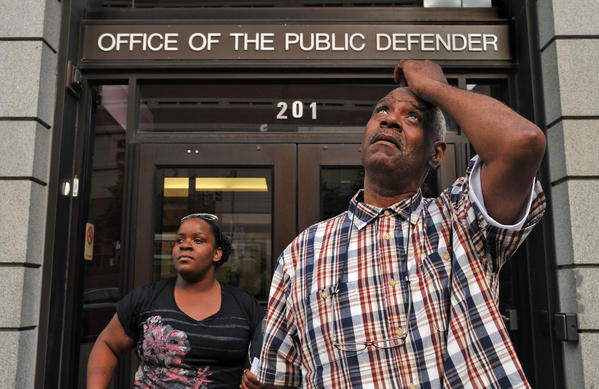 Liston Noble looks up at the new high-rise office buildings across the street from the Office of the Public Defender, which hadn't been built when he went to jail. He was briefly at the Public Defender's Office after walking out of the Circuit Court building today as a free man. Behind him is Kiaria Noble, one of three relatives who accompanied him. Noble is one of five men sentenced to life in prison in the 1960's and '70's were released today after an appeals court ruling in the Unger case.