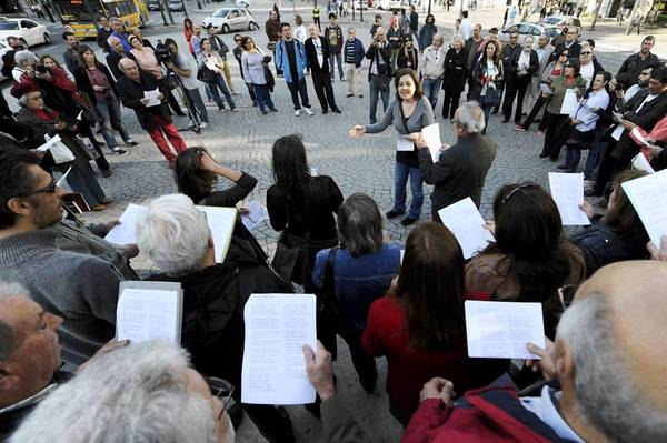 Opera singer Ana Maria Pinto, center of circle, leads an informal choir during an anti-austerity protest in Portugal.
