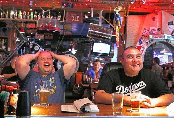 Dodgers fans Jose Zuniga, left, and Gabriel Aguilar react at Barneys Beanery in Burbank as they watch the team play the Philadelphia Phillies. Fans have poured into dining and drinking spots that show games.