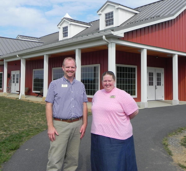 Aaron Ziebarth, left, executive director of Joy El Ministries, and Miriam Ankerbrand, Joy El's development coordinator, stand in front of the worship building at Joy El Camps & Retreats in Greencastle, Pa.