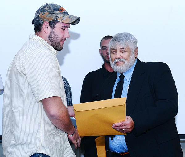 Barr Construction Institute graduate Derrick Faith, left, of Clear Spring, receives his electrical apprenticeship certificate from Carrol Shifler at a graduation banquet Thursday evening at the Ramada Plaza on Underpass Way.