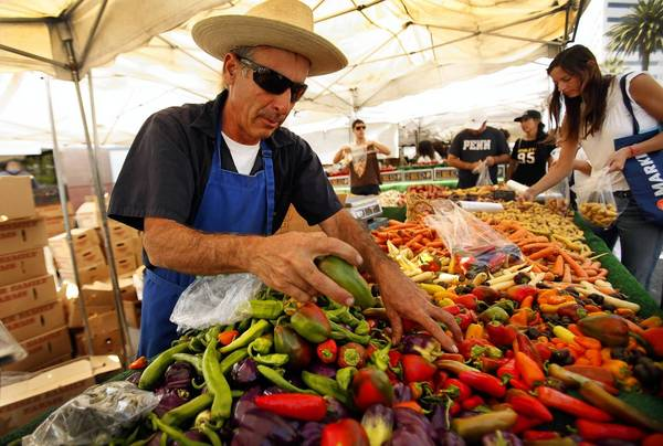 Alex Weiser of Weiser Family Farms sorts through his produce at his stand in the Santa Monica Farmers Market.