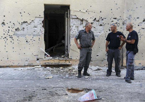 Israeli policemen on Thursday stand in front of a house damaged by a rocket fired from Lebanon in Moshav Shavei Zion, Israel.