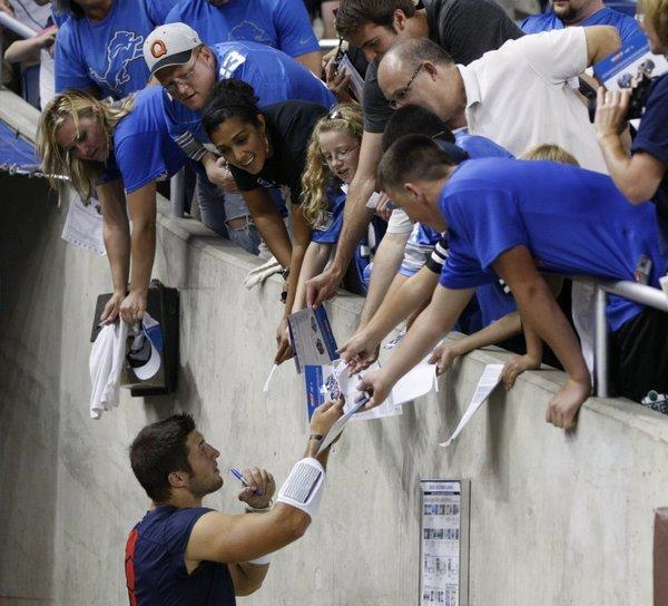 Patriots quarterback Tim Tebow signs autographs before New England's exhibition game against the Detroit Lions at Ford Field in Detroit.