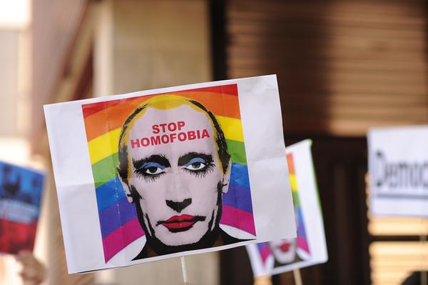 A protestor holds up an image representing Russian President Vladimir Putin wearing lipstick during a protest against Russian anti-gay laws.