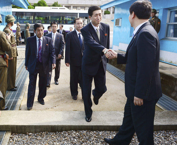The leader of the North Korean delegation, Park Yong Il, shakes hand with his South Korean counterpart Lee Duk-haeng, right, as he arrives in the border village of Panmunjom for talks on resuming family reunions between the two nations.